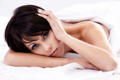 In bed. Closeup portrait of a young brunette woman lying in bed Royalty Free Stock Photos