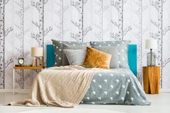 Bed against forest motif wallpaper. Close-up of cozy bed with gray bedsheets and beige blanket against white wallpaper with forest motif stock image
