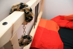 A bed with attached handcuffs. A wooden bed with leopard fur handcuffs locked onto it royalty free stock images