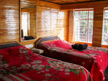 Bed and backpack in a log cabin Royalty Free Stock Image