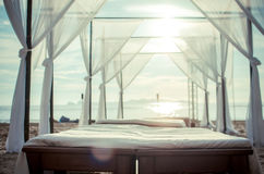 Bed on the beach pastel backlight sunset lighting lens flare Royalty Free Stock Images