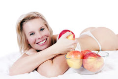 Cheerful girl in bed surrounded by apples. Royalty Free Stock Photos