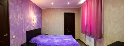 Bed in bedroom in shades of lilac Royalty Free Stock Photo