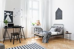 Bed and black chair at desk in kid`s room interior. With posters and plush toy on window sill. Real photo stock photo