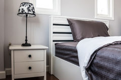 Bed with black sheet and lamp. In white bedroom Stock Photo