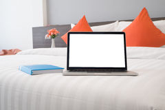 Bed with blank screen laptop, book,  beautiful flower at bedroom Royalty Free Stock Image