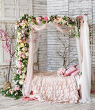 Bed, braided and twined with flowers royalty free stock image