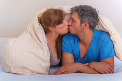 Bed and breakfast. Bedroom couple in hotel bed kissing stock image
