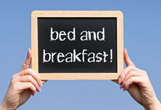 Bed and breakfast sign. Bed and breakfast chalkboard sign being held by hands Royalty Free Stock Photos