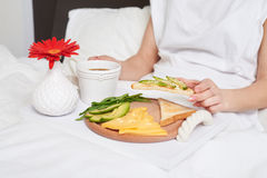 Bed breakfast with tea, avocado, cheese on tray decorated with r. Cropped shot of bed breakfast with black tea, avocado, cheese and bread, salad rocket on tray Royalty Free Stock Photo