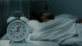 Bed clock showing midnight near sleeping man in bed, rest hours, healthy sleep. Stock footage stock footage