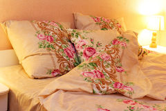 Bed clothes. Close up of bedding sheets and pillow on bed and lamp Royalty Free Stock Images