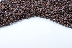 Bed of coffee beans. Coffee beans on a white table top stock photography