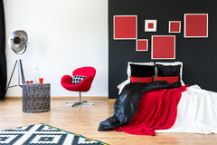 Bed with contrast colored pillows. Modern interior with red paintings on black wall above king-size bed with contrast colored pillows Royalty Free Stock Photography