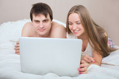 Bed couple happy on laptop computer in bedroom. Stock Image