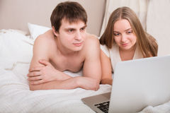 Bed couple happy on laptop computer in bedroom. Stock Images