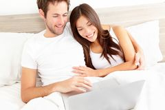 Bed couple with laptop Stock Images