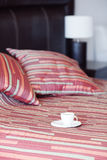 Bed,a cup of tea on the bedside table and lamp Royalty Free Stock Image