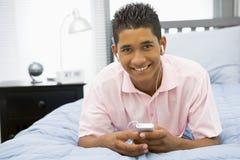 bed den lyssnande liggande spelare mp3 för pojken som är tonårs- till Royaltyfri Fotografi