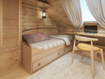 Bed and desk in the children's room in a log house in the attic Stock Image
