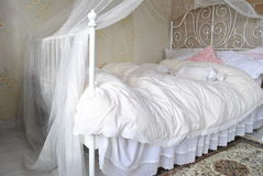 White bad with laces and decors. Fantastic, very comfortable bed designed in a shabby style, in whites and laces. PiÄ™knie urzÄ…dzone w stylu shabby stock photos