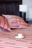 Bed, een kop thee op de bedlijst en lamp Royalty-vrije Stock Afbeelding