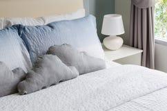 Bed en hoofdkussens met witte lamp Stock Afbeelding