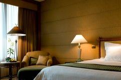 Bed en leunstoel in een vijfsterrenreeksslaapkamer Royalty-vrije Stock Afbeelding