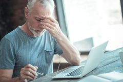 Serious unshaken man sitting and feeling bed himself. Bed feeling. Serious unshaken aged man sitting by the table touching to his head and feeling bed himself Royalty Free Stock Photo