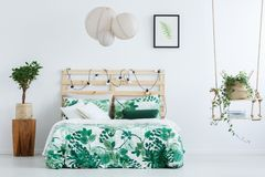Bed with floral overlay. Small tree in pot on wooden designer table next to bed with floral overlay in inspiring bedroom with handmade swing royalty free stock photos