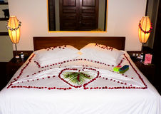 Bed with flowers. Photo of the bed with rose petals and palm leaf Royalty Free Stock Photo