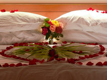 Bed with flowers. Photo of the bed with rose petals and palm leaf Royalty Free Stock Photography