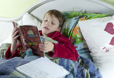 In bed with the flu doing schoolwork. Young caucasian boy iIn bed with the flu doing schoolwork Royalty Free Stock Image