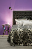 Bed in front of a purple wall Royalty Free Stock Image