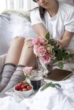 bed frukostromantiker En bukett av rosor och ett doftande morgonkaffe nya jordgubbar Bra morgon i den skrynkliga sängen Arkivfoto