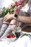 bed frukostromantiker En bukett av rosor och ett doftande morgonkaffe nya jordgubbar Bra morgon i den skrynkliga sängen Royaltyfri Fotografi
