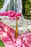 Bed in garden for lovers. Bed with red blanket in the garden for lovers Stock Images