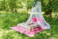 Bed in garden for lovers. Bed with red blanket in the garden for lovers royalty free stock photos