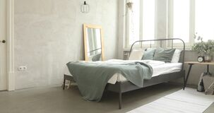 Well decorated bedroom morning. Bed with green coverlet stands in bright bedroom with large French windows mirror and small bedside lamp with a plant and alarm stock video