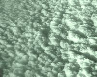 Bed of Greenish White Clouds in Sky captured from Air. This is a photograph of a bed of white clouds spread in the sky, captured while traveling in air Stock Photography