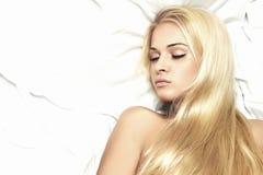 bed.hair的care.beauty美丽的性感的白肤金发的妇女 免版税库存图片
