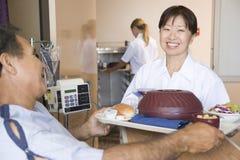 bed hans patient serving för målsjuksköterskan arkivfoto