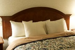 Bed Headboard. A headboard with white pillows, set against a plain wall. generic hotel room type of photo stock photo