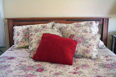 A bed: headboard, pillows, bedspead. A simple bed with pretty, flowery bed cover (quilt) and pillows covered in shams Stock Images