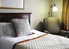 Bed in hotel room. Bed and lamp in clean, modern, standard hotel room Royalty Free Stock Photos