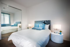 Bed with a huge mirror beside a lamp and table. Which is rounded shape, the sheets are white with blue pillows near the square light stock photography