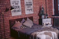 Bed in the interior with New Year decorative elements in the loft style. Bed in the interior with Christmas decorations and a Christmas tree Stock Photography