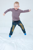 Bed jumping boy Stock Images
