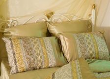 Bed linen. Bedding - pillow and blanket in the new clothes on the bed Royalty Free Stock Photos