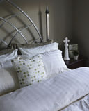 Bed Linens and Pillow Cases. Crisp and comfy linens in neutral shades of green and off white set an earthy tone in a guest bedroom Stock Photography